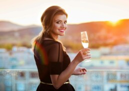 Beautiful Woman on a Balcony with Champagne and Sunset Background