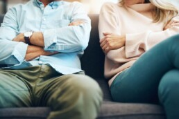 Couple Sits on Couch with Arms Folded - Imbalance in Your Relationship