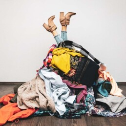 Woman Buried Under Pile of Clothes - Declutter Your Mind